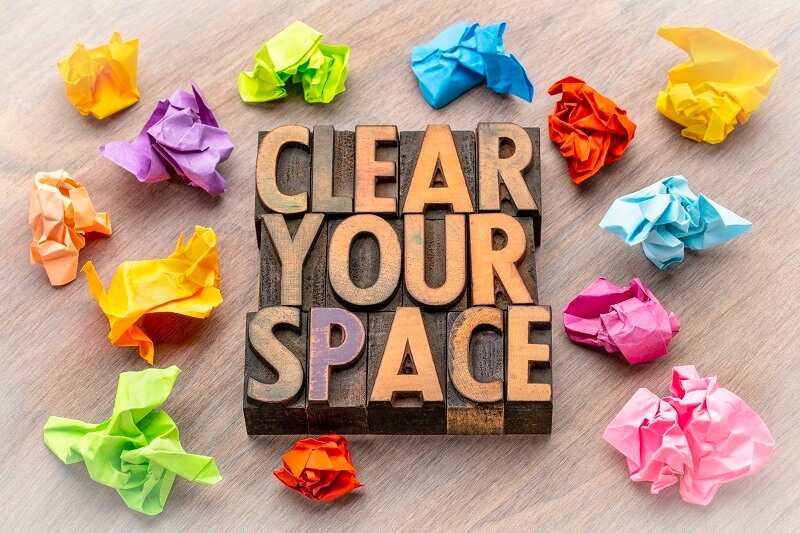 wood blocks spelling clear your space surrounded by colorful crumpled paper on wood background