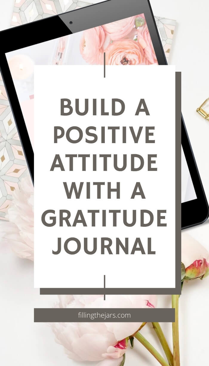 pastel journal and digital tablet on white background with tulips and text overlay build a positive attitude with a gratitude journal