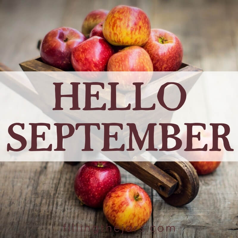 text hello september on white stripe over small decorative cart full of apples on wood table