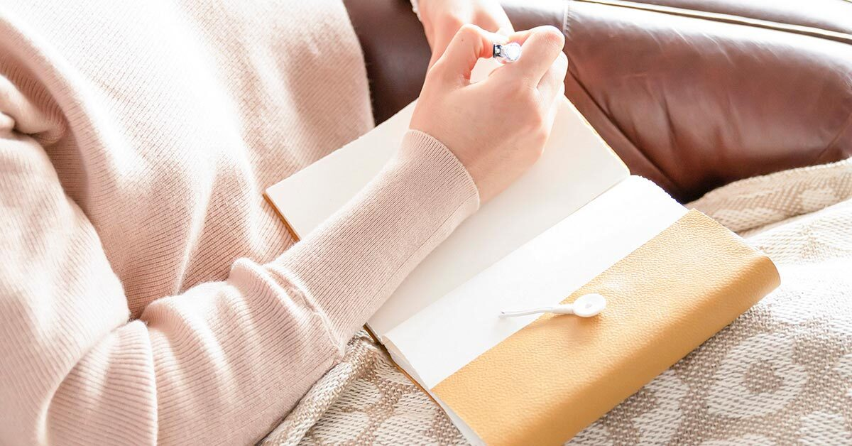 woman in pink sweater with blanket sitting on brown leather couch while writing in journal