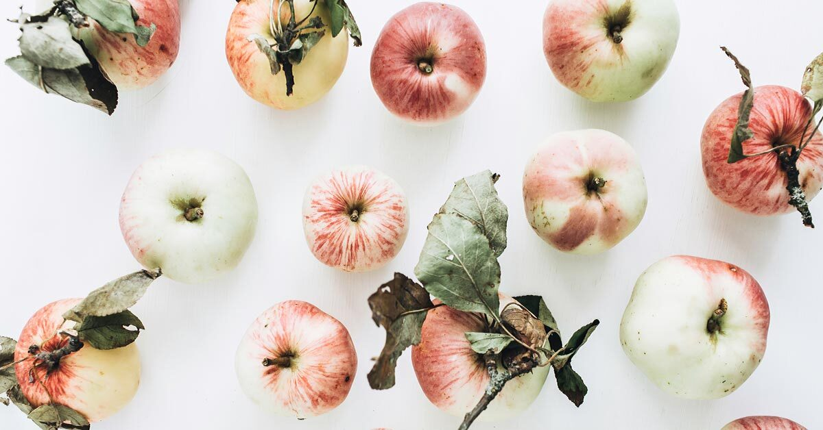 pale ripe apples scattered across white background