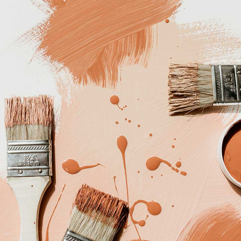 paint brushes and paint swishes and drips in warm orange autumn tones