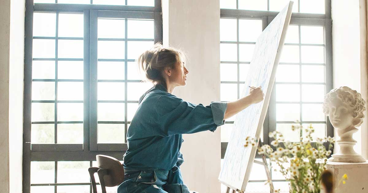 blond woman in blue denim shirt painting in front of sun shining through large windows