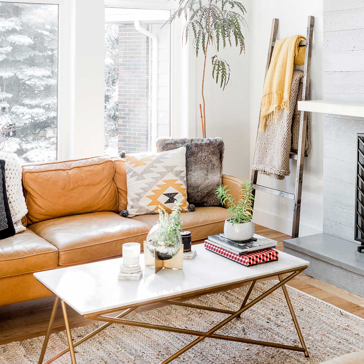 clutter-free white living room with modern coffee table and brown leather couch with cozy pillows and throws