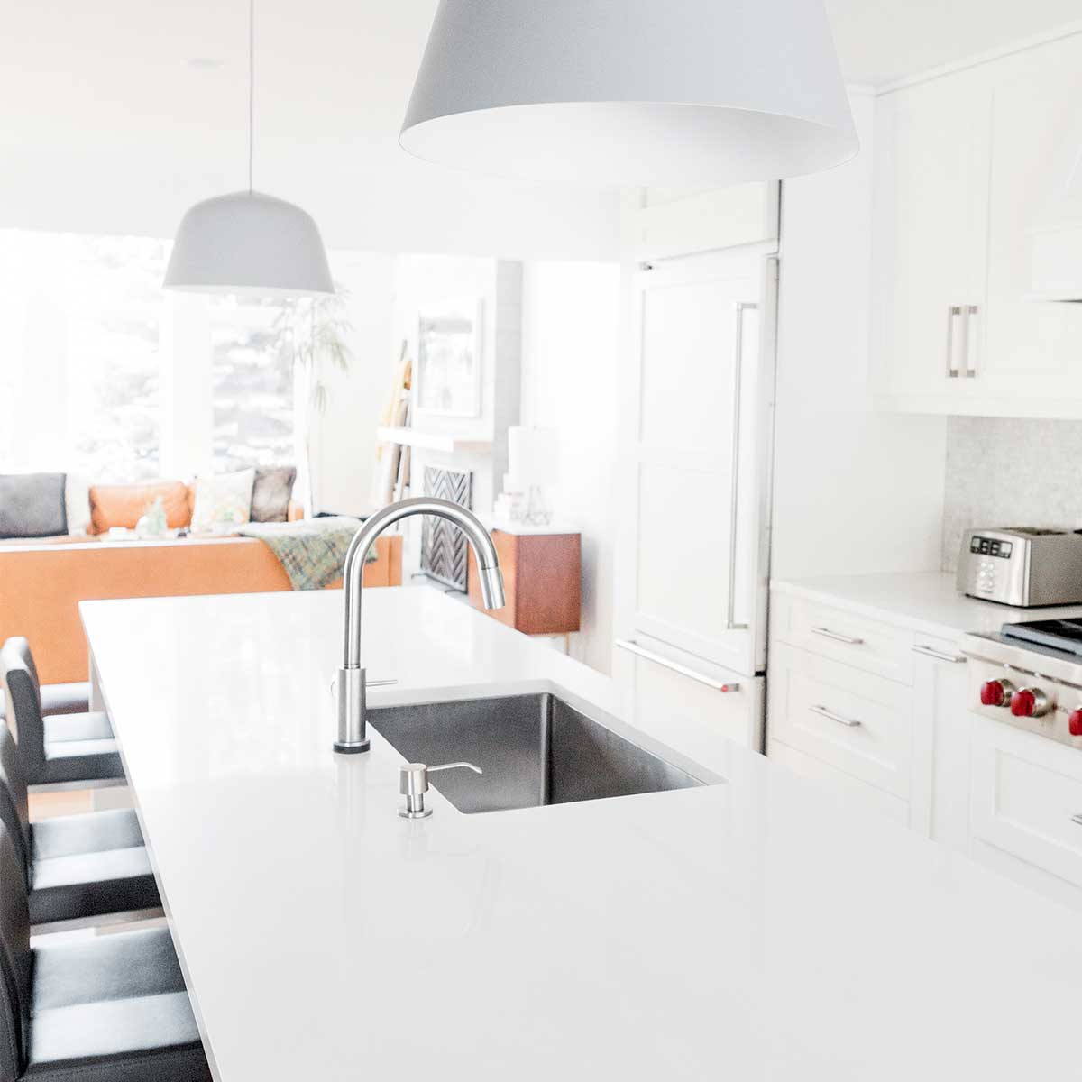 white kitchen with stainless sink and black bar stools