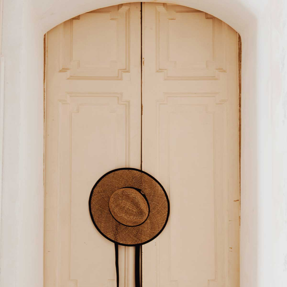 painted raised panel double door set behind white walls with straw hat hanging on handle