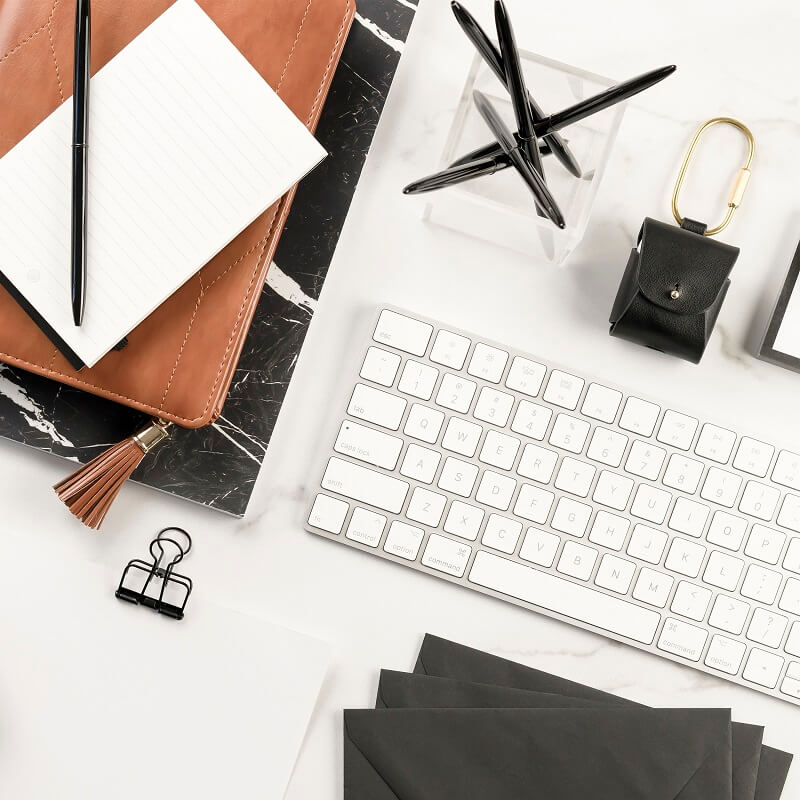 flatlay of desk supplies journals and keyboard on white background