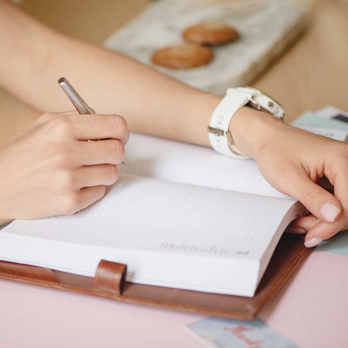 woman wearing white watch and writing in journal on desk