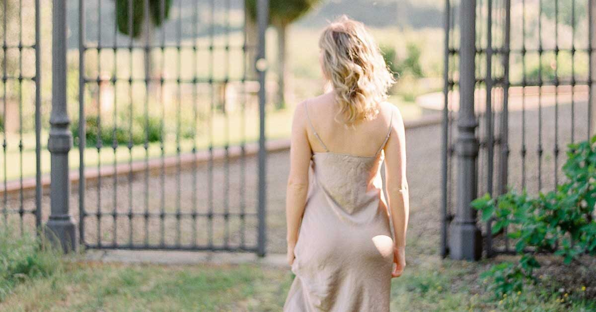 young woman with blonde hair wearing beige dress looking away through open iron gate