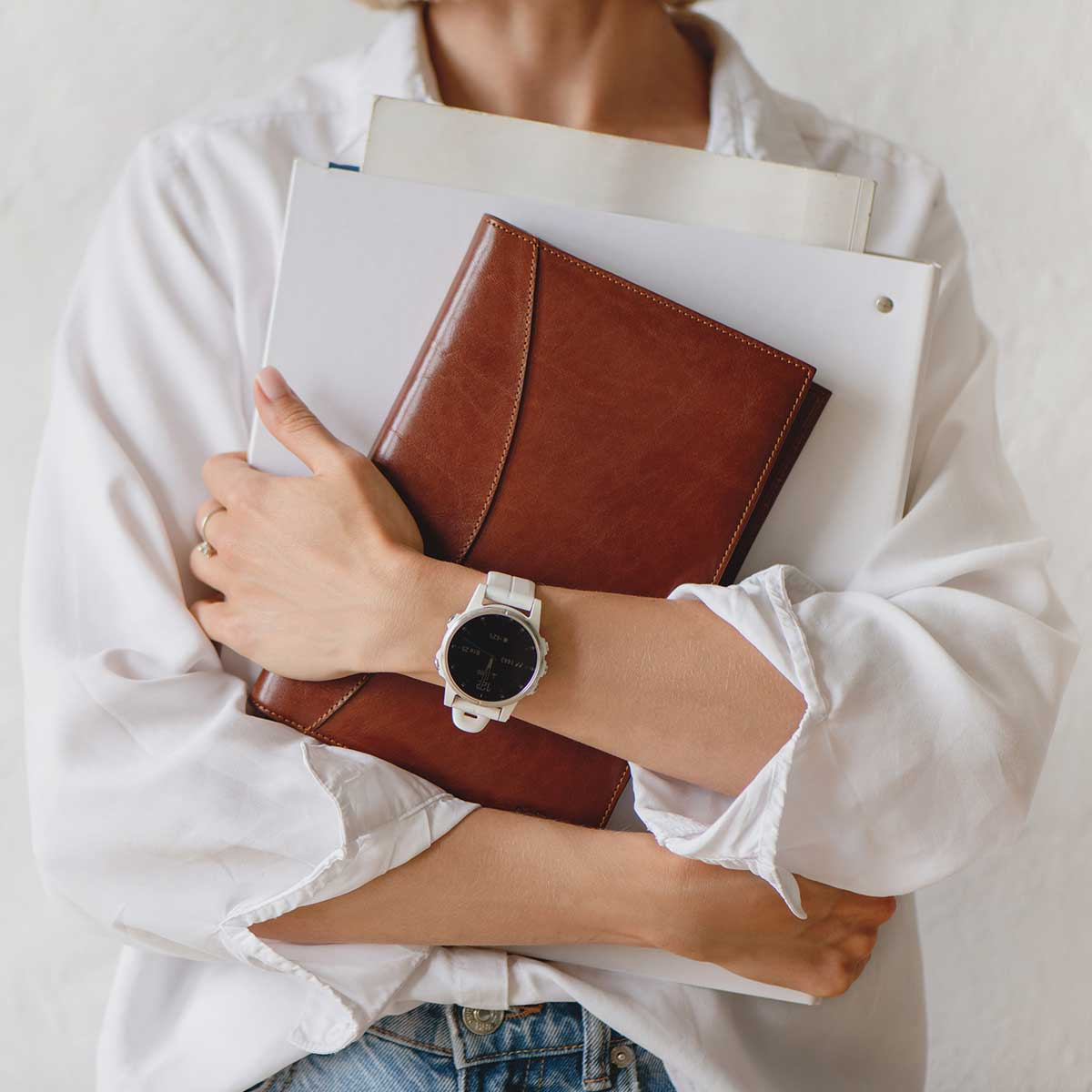 woman wearing white watch and white shirt holding leather journal and white binders