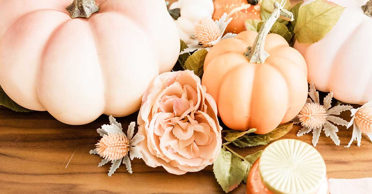 pale orange pumpkins and flowers with greenery lying on wood table