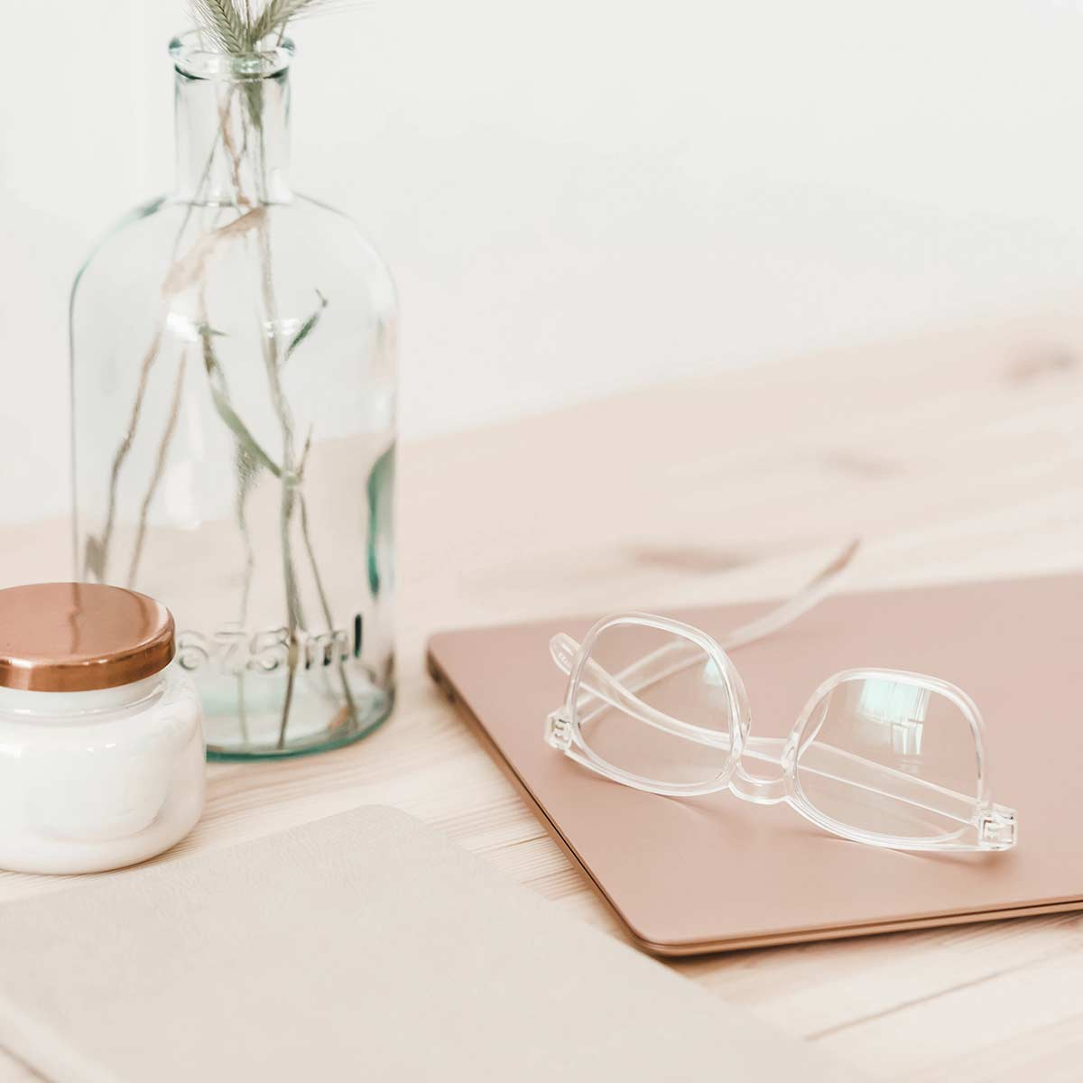 glasses, laptop, journal, glass jars on wood table