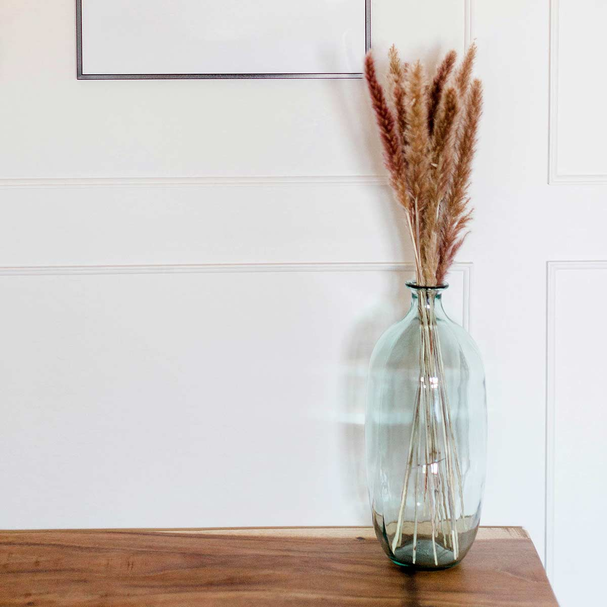 green glass vase with dried grasses on clutter-free wood table against white wall