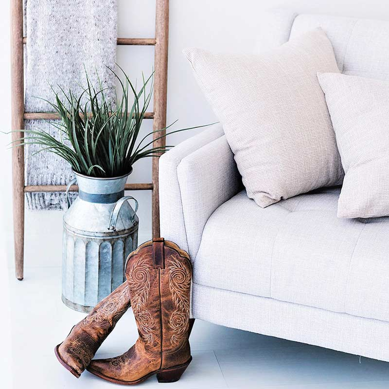 white living room with white couch, blanket ladder, rustic metal milk can, brown cowboy boots