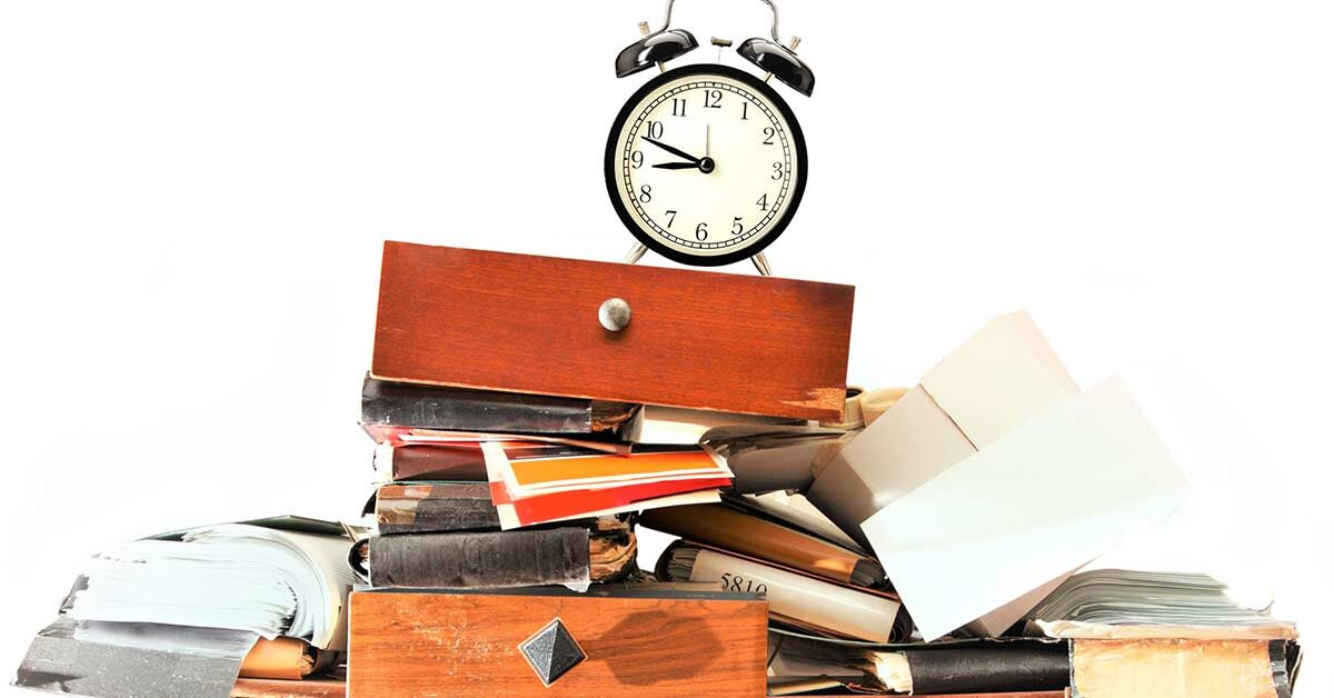 Clock sitting on top of clutter pile of books, papers, and desk drawers against white background.