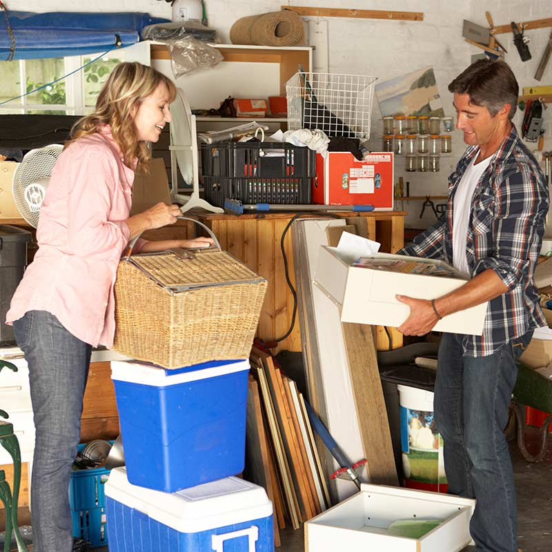 man and woman clearing out cluttered garage