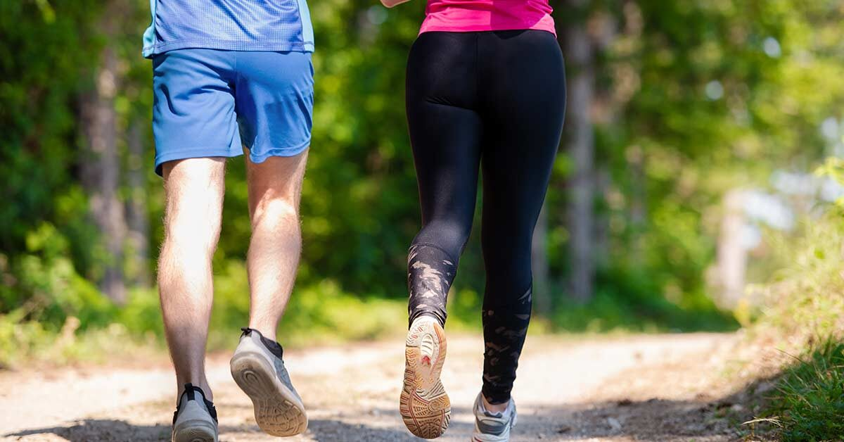 man and woman running on sunny dirt trail