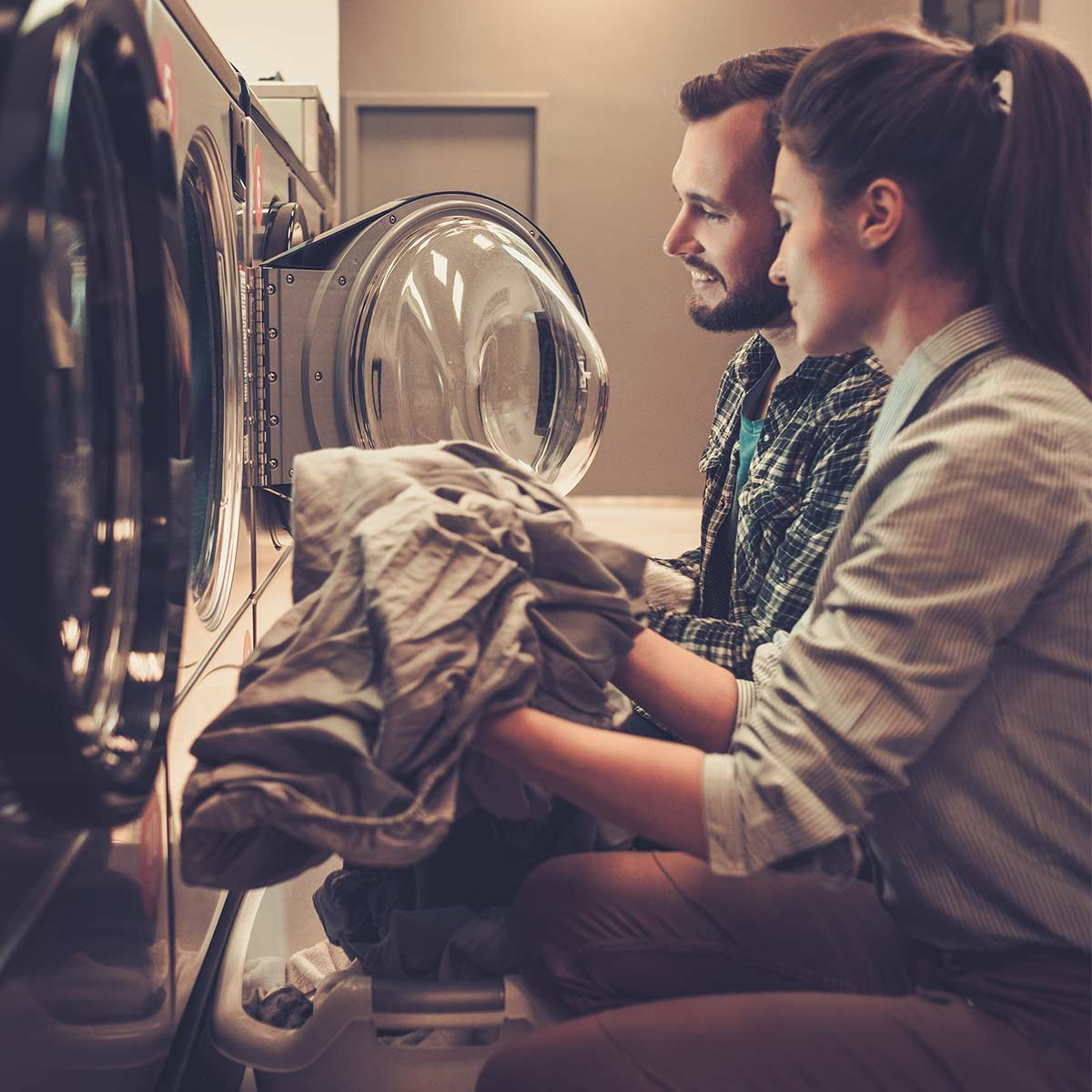man and woman sitting in front of dryers and folding laundry together