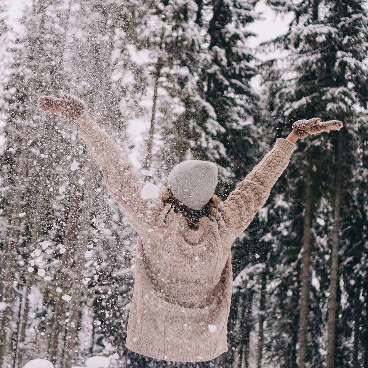 woman in hat and pink sweater enjoying an intentional life outdoors in the snow