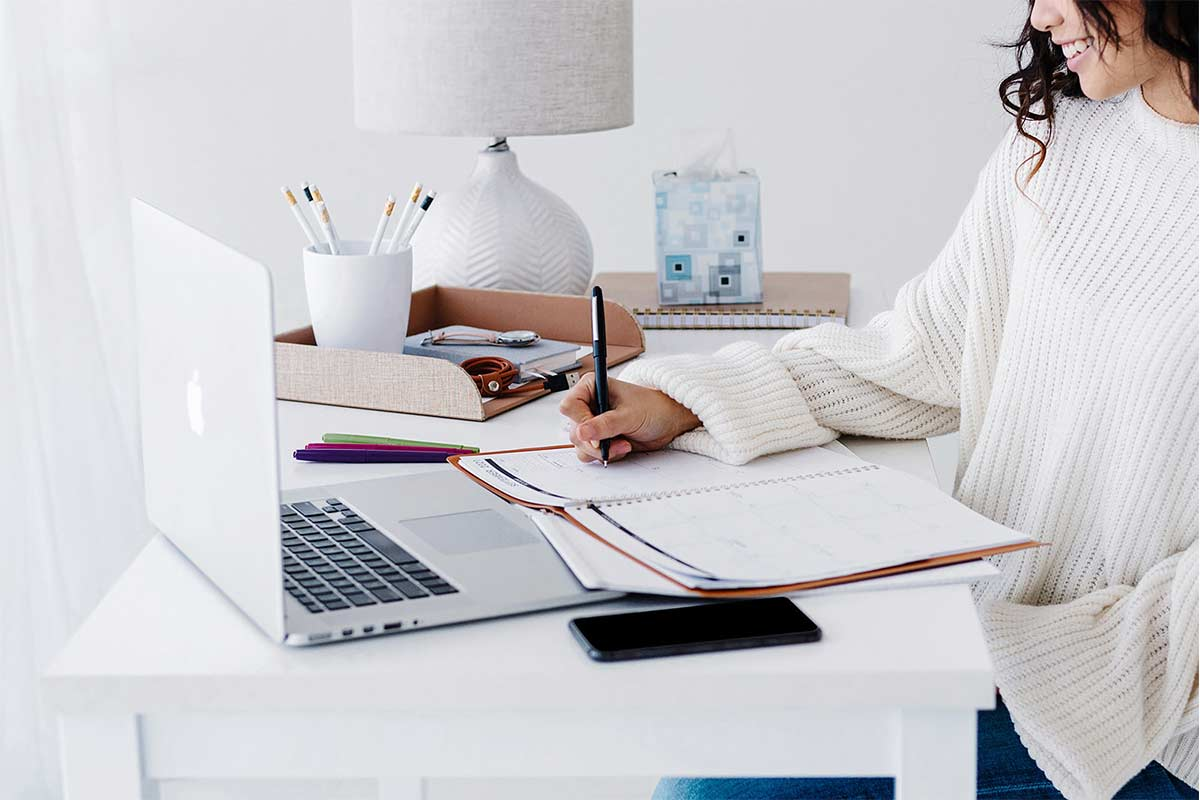 woman wearing white sweater working at desk in white home office