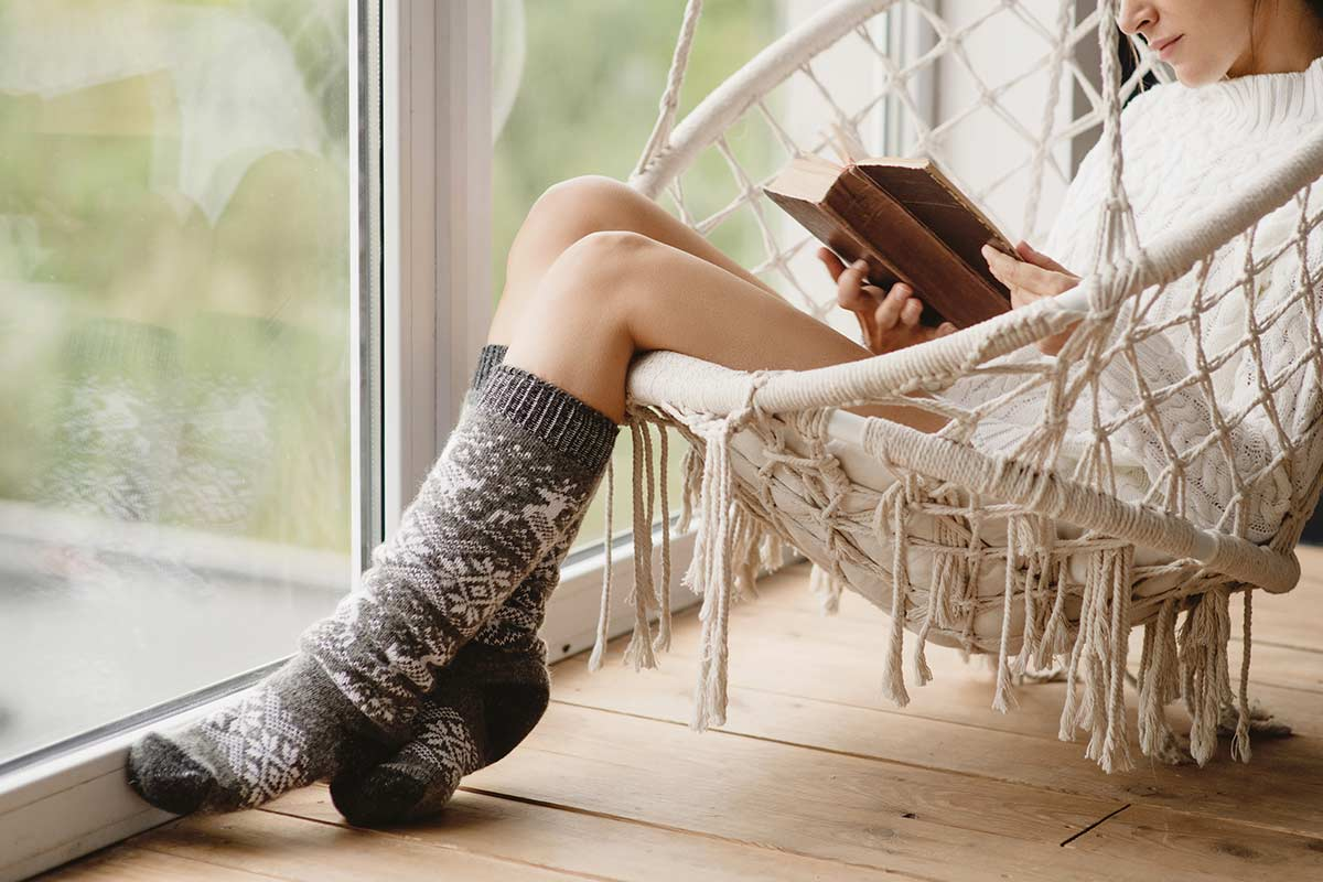 woman sitting in swing chair next to sliding doors while reading