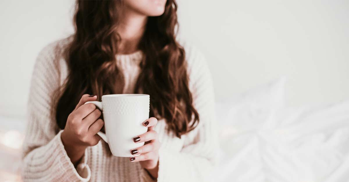 woman with long dark hair wearing white sweater and holding white coffee mug