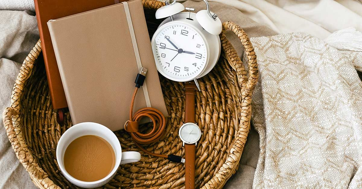 shallow woven basket with watch, coffee, clock, and journals sitting on linens