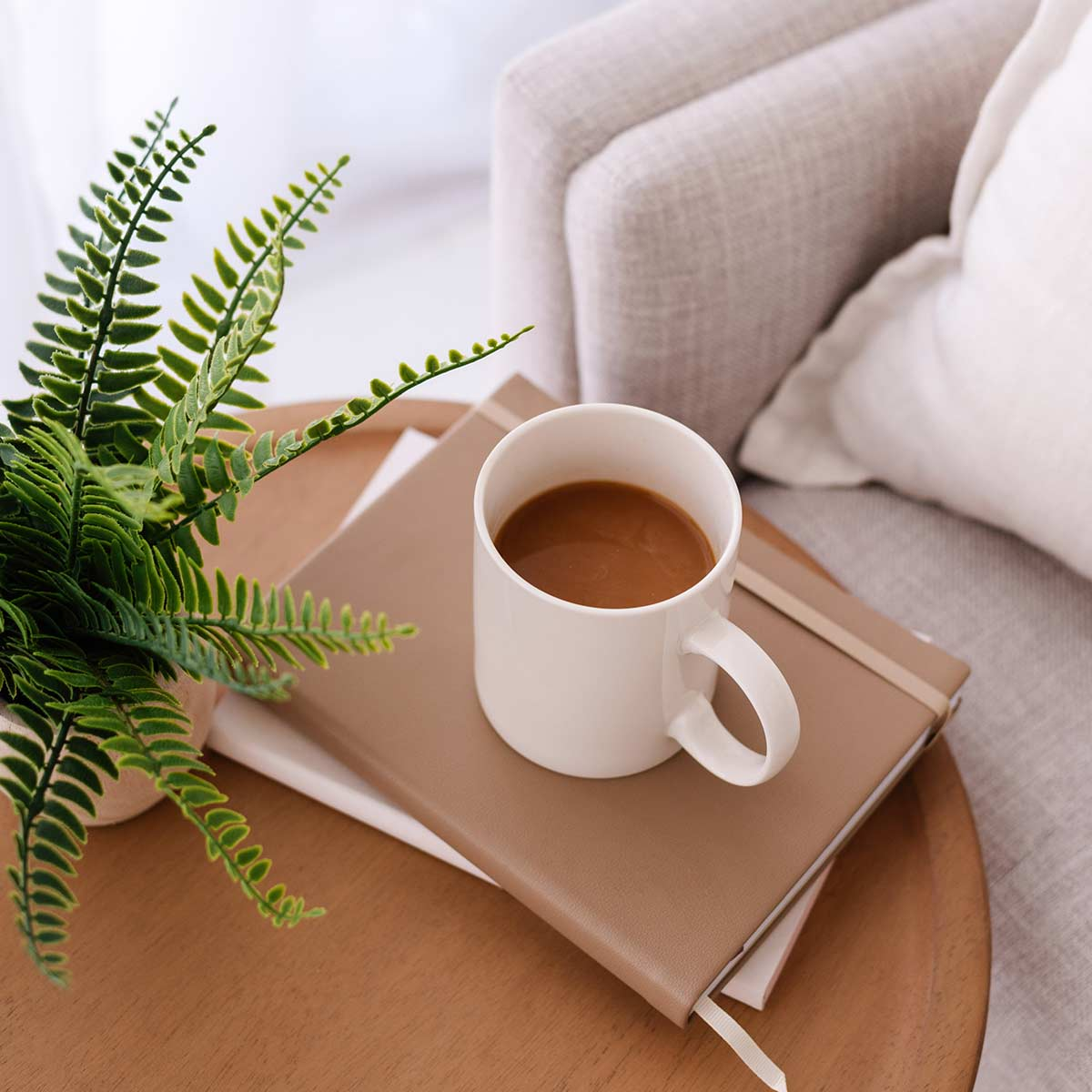 White coffee mug on journal stack sitting on round wood table next to plant in neutral-decor living room.