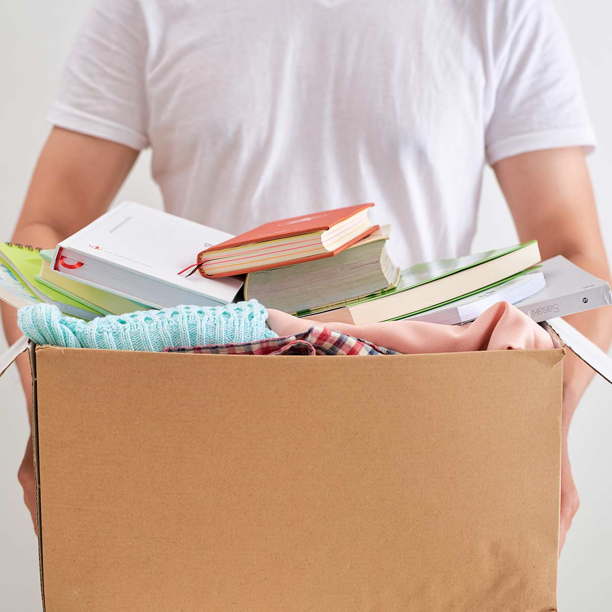 Man in white t-shirt holding cardboard box of decluttered items.