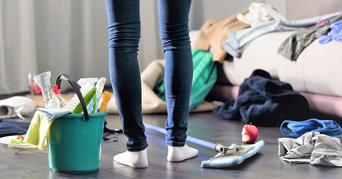 Woman in jeans and white socks standing in cluttered bedroom next to cleaning supplies on wood floor.