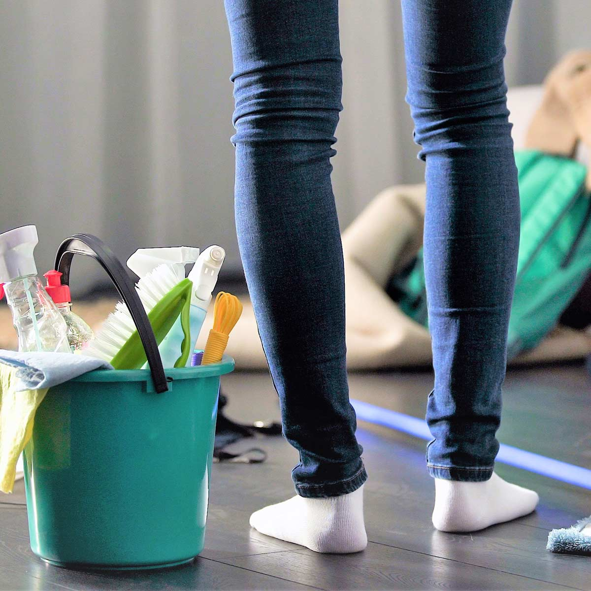 Woman in jeans and white socks standing in cluttered room next to cleaning supplies on wood floor.