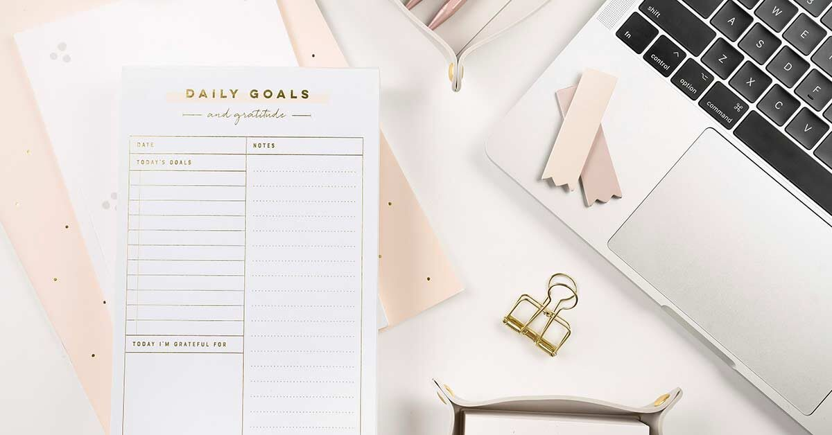 Daily goals planner and office supplies on white desktop next to laptop computer.