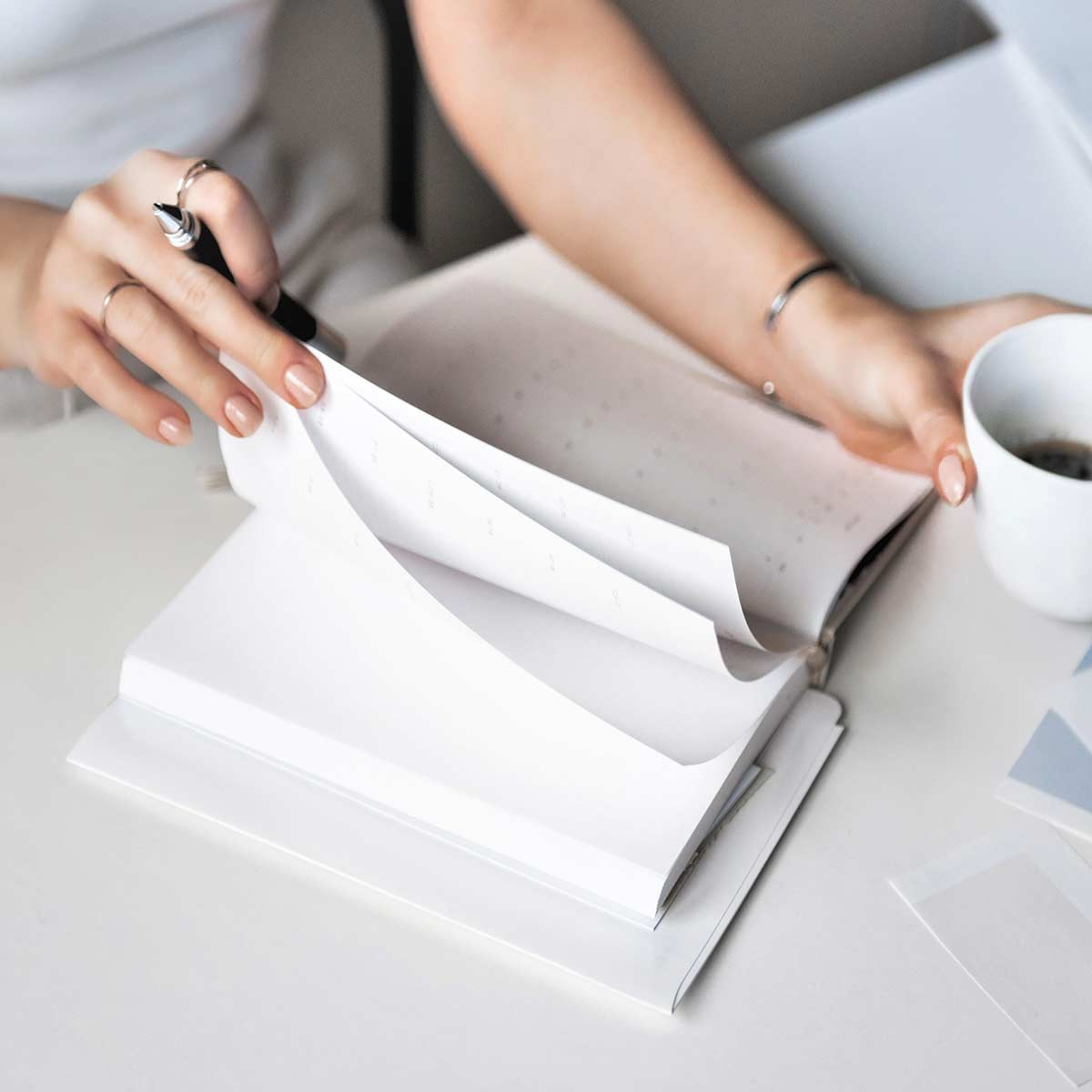 Adult woman sitting at white desk holding coffee cup while preparing to do daily journaling.