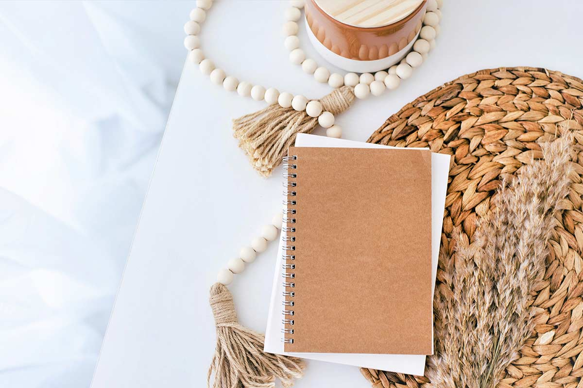 Journal, notebook, and decorative items on white desk.