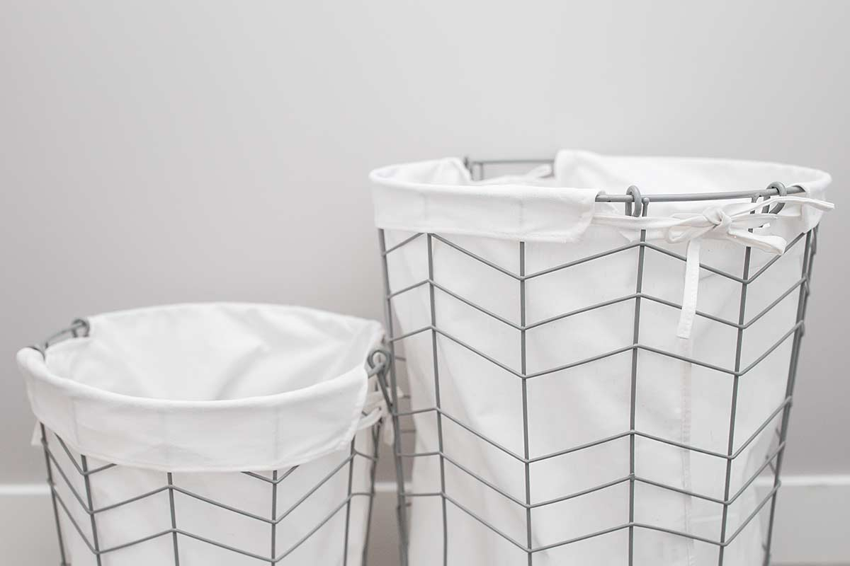 Two wire bins with fabric liners against white wall.