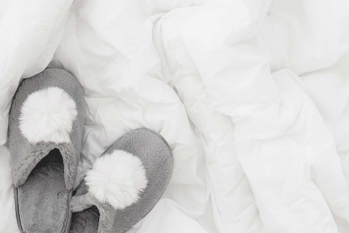 Gray slippers on fluffy white bedding.