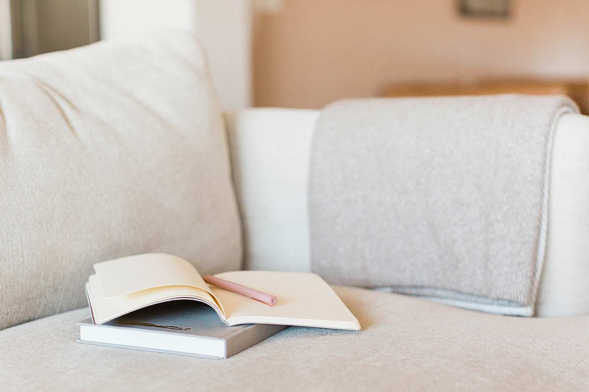 Hardcover book and open journal with pink pen sitting on white fabric cushion with folded woven gray blanket over arm of couch.