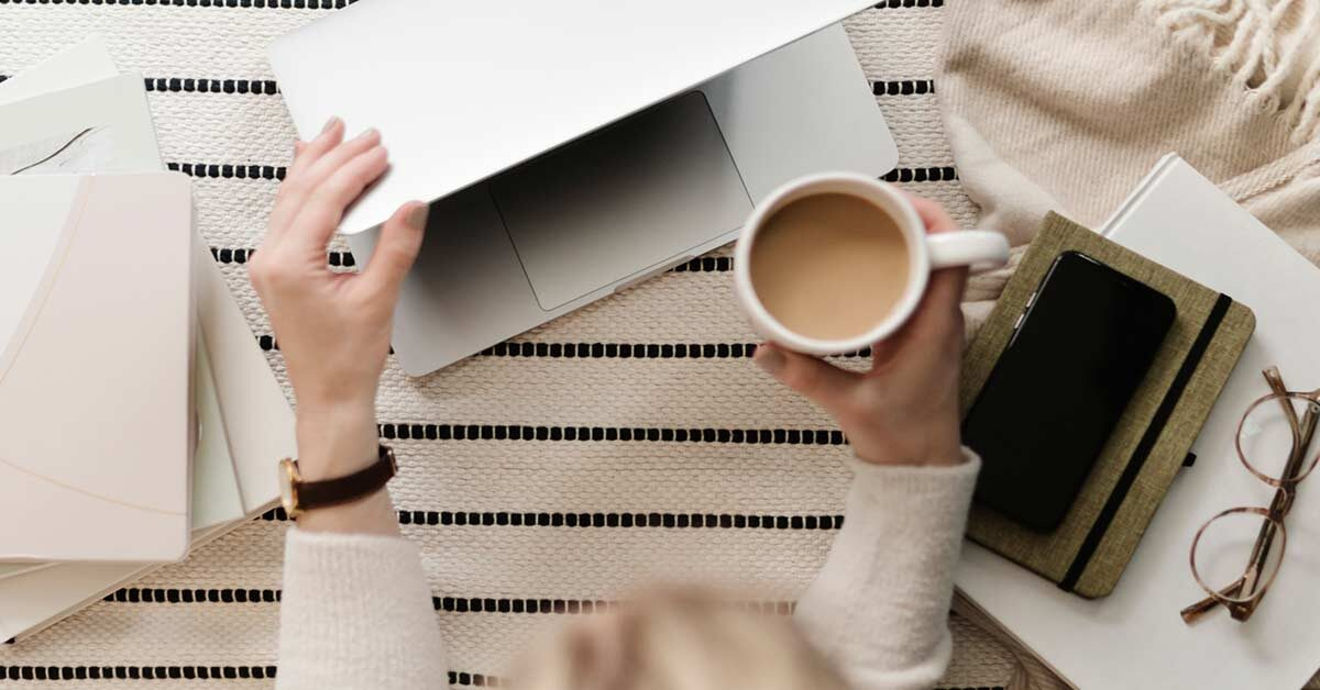 Woman sitting at table with striped tablecloth and books while holding coffee mug and opening laptop computer.