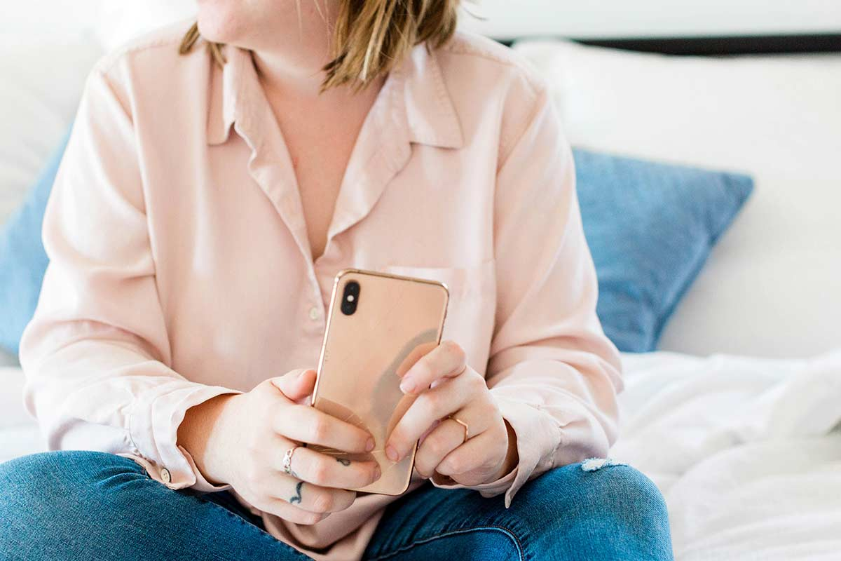 Woman in pink blouse and jeans sitting down while holding pink phone.