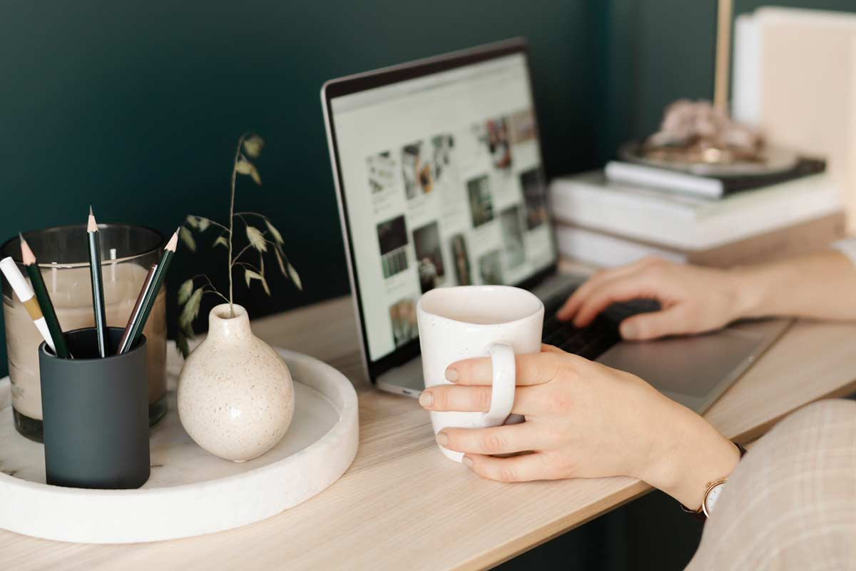 Woman sitting at wood desk and holding coffee mug while scrolling on laptop computer.