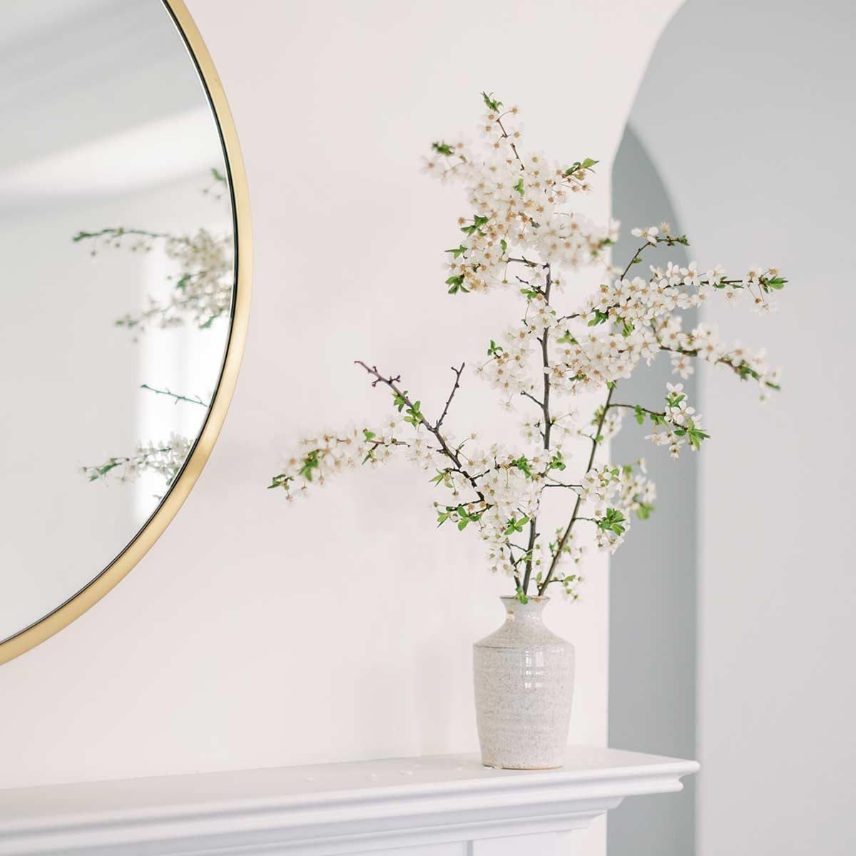 Spring flowering branch in white vase on clutter-free white mantel.