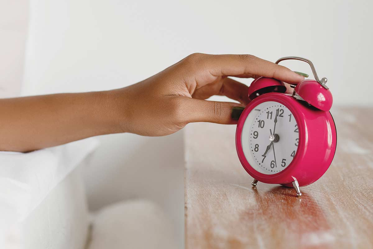 Woman's hand reaching to turn off the alarm on pink clock.