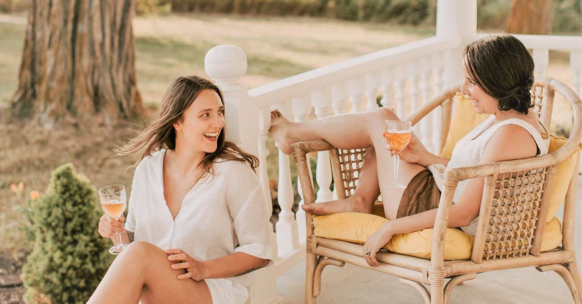 Two women laughing and sitting on a porch.