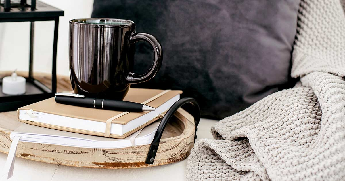 Journals and black coffee mug on wood tray next to knit blanket and throw pillow.