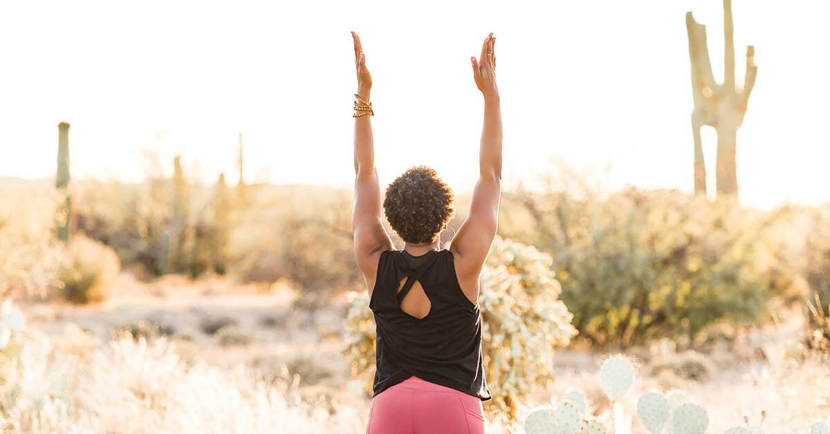 Rear view of black woman in black tank and pink leggings raising arms while doing yoga in desert on sunny morning.
