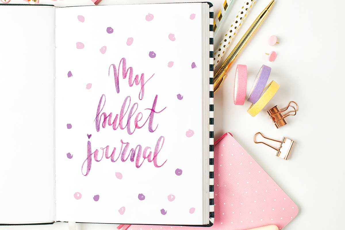 Pink and purple lettered bullet journal page in open journal lying on white desk with pens and other desk supplies.