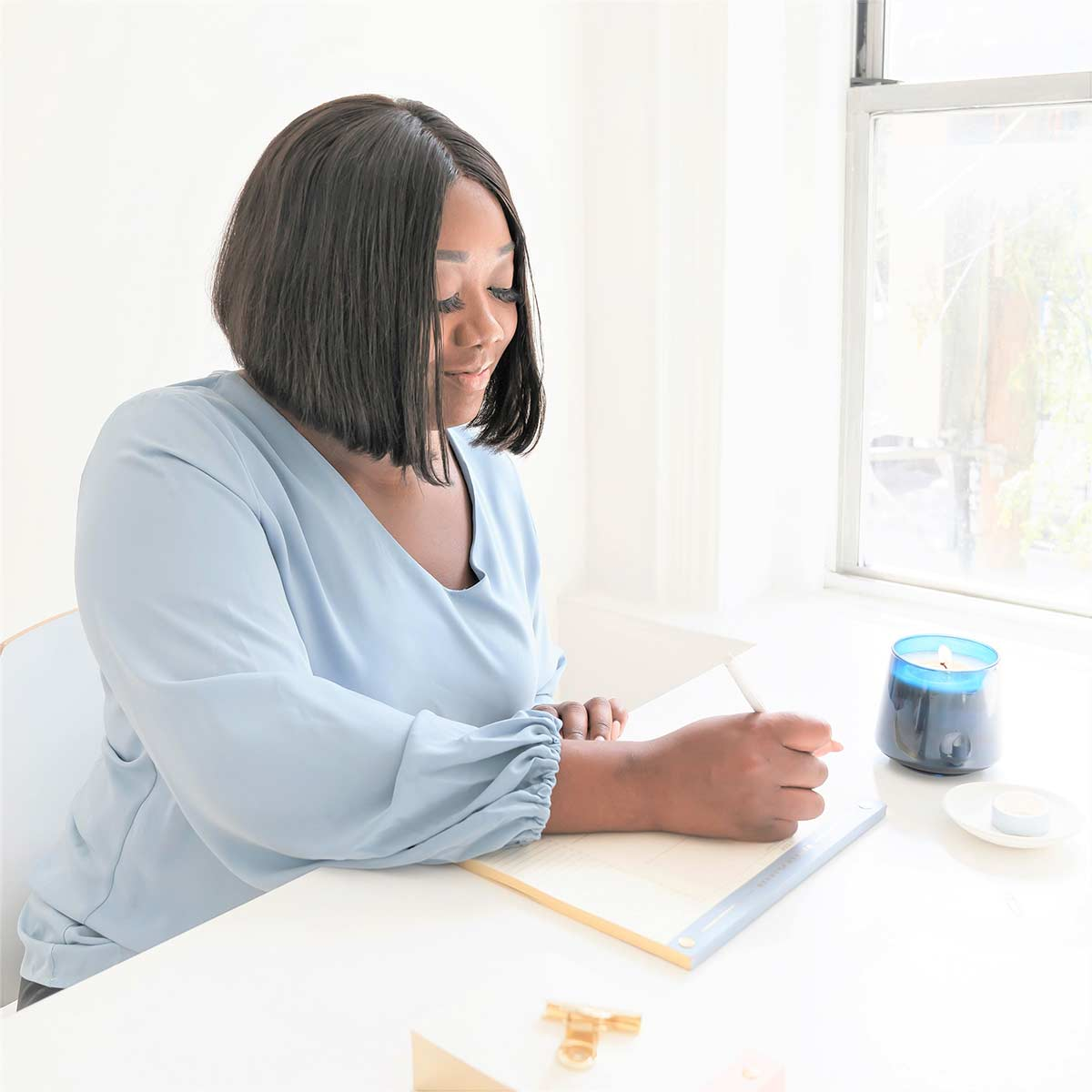 Beautiful Black woman in blue top sitting in bright home office and preparing to do creative journaling.