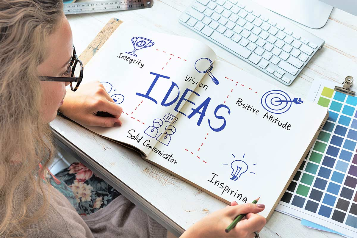 Woman working on creative mind map journal.