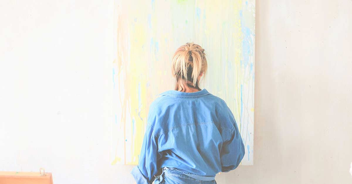 Blonde woman in denim clothing finding creativity by painting a canvas hung on white wall.
