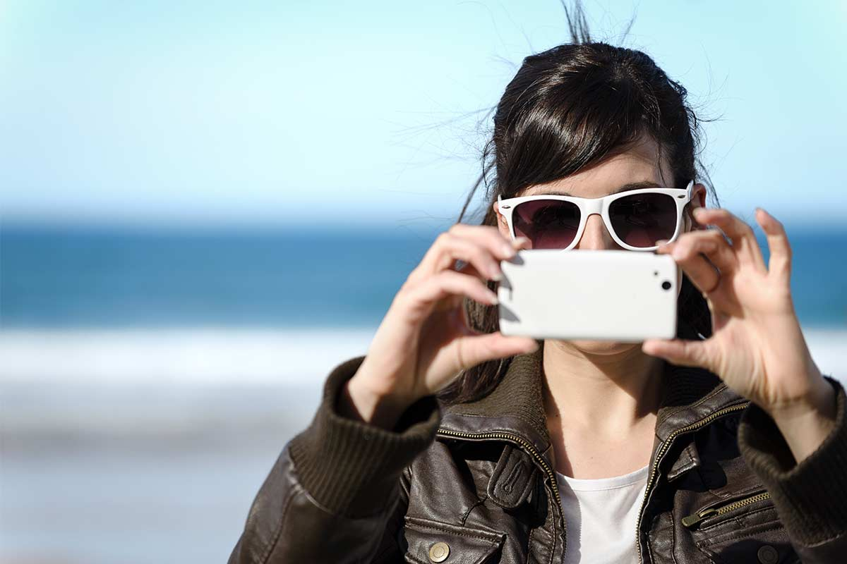 Woman wearing white sunglasses and leather jacket standing outdoors and holding phone up to take a photo.